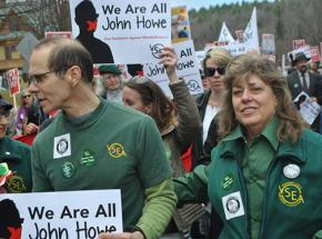 John Howe (left) marches with supporters in a protest defending his job