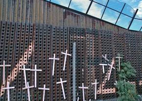 A section of the border wall in Nogales, Ariz., with crosses to memorialize people who died attempting to cross