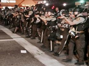 Police clad in riot gear move down West Florissant in Ferguson, Mo.