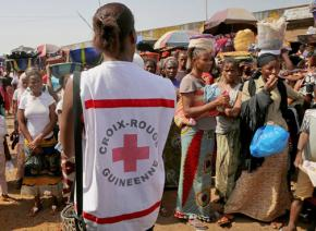 A Red Cross volunteer gives instructions about Ebola to a crowd in a city in Guinea