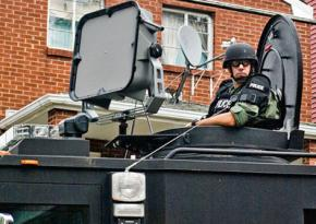Philadelphia police ride in an armored vehicle down a residential street