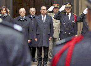 François Hollande stands for a moment of silence at police headquarters in Paris