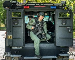A SWAT officer poses in the back of an armored vehicle
