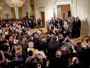 Barack Obama signs health care legislation in front of Democratic lawmakers in the East Room of the White House