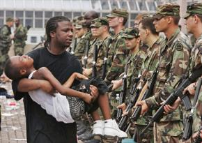 A Katrina survivor holds his young son in front of a line of soldiers