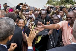 Barack Obama (front left) greeted by large crowds on his arrival in Kenya