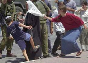 Israeli settlers, protected by IDF soldiers, attack a Palestinian woman