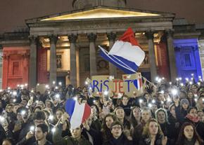France's flag flies at a vigil in London in sympathy with the victims of the Paris attacks