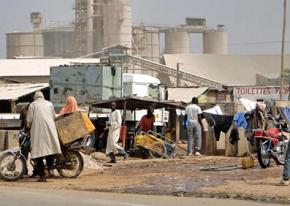 People work and trade along a dirt road outside a cement factory in Cameroon
