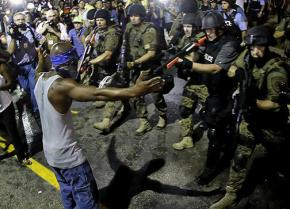 Police train their weapons on a protester in Ferguson, Missouri