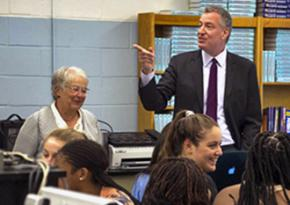New York City Schools Chancellor Carmen Farińa (back left) and Mayor Bill de Blasio (standing) visit a school