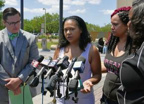 Laniya Miller's mother speaks to reporters, surrounded by family and supporters