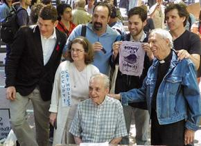 Father Daniel Berrigan (seated) joins a solidarity demonstration for Occupy activists facing charges for civil disobedience