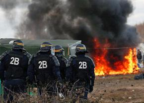 French riot police oversee the demolition of refugee shelters at a camp in Calais