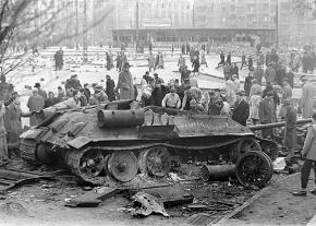 Hungarian workers gather around a gutted Soviet tank in Budapest