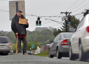 A homeless man stands at an intersection in Portland, Maine