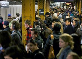 Commuters crowd onto a New York City subway platform