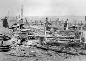 Survivors of the 1914 Ludlow Massacre survey the ruins of the strikers' protest camp