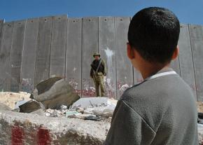 A Palestinian child looks on at Israel's apartheid wall in the West Bank