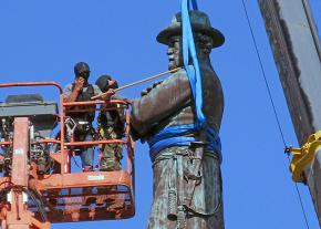 Workers remove a statue of Confederate General Robert E. Lee from a New Orleans square