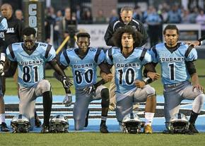 Lansing Catholic High School football players take a knee during the national anthem