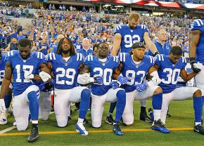 Members of the Dallas Cowboys take a knee during the national anthem