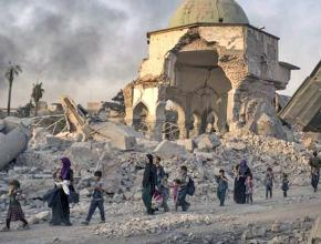 Civilians walk through the streets of Mosul after months of U.S. air strikes
