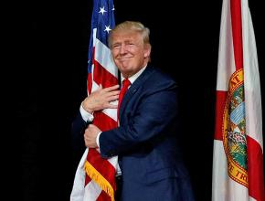 Donald Trump hugs the American flag before a speech in Tampa, Florida