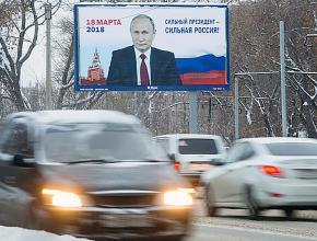 Commuters pass an election billboard on a Moscow highway