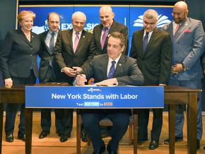 Gov. Andrew Cuomo signs a bill, flanked by union leaders, including UFT President Michael Mulgrew (directly behind Cuomo)
