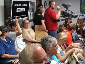 Protesters attend a city council meeting in Nelsonville, Ohio, to demand the firing of a racist police officer