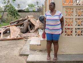 A resident of Loíza, Puerto Rico stands outside her damaged home in the aftermath of Hurricane Maria