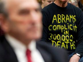 A protester sits behind Elliott Abrams during a House Foreign Affairs Subcommittee hearing